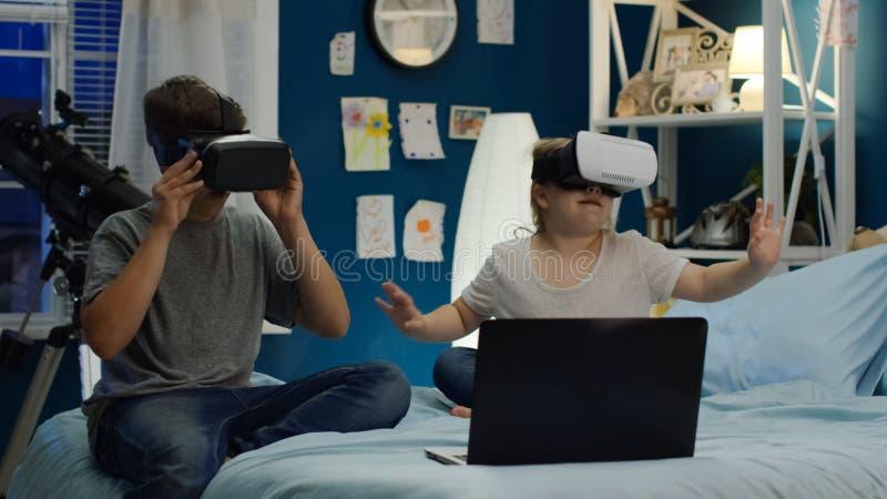 Bambini che giocano video gioco negli occhiali di protezione di VR sul letto immagini stock libere da diritti