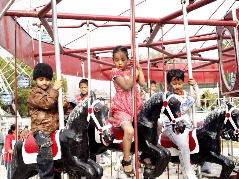 Bambini che godono ?del carosello del cavallo di volo? fotografia stock