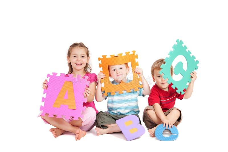 Bambini che hanno divertimento imparare ABC di alfabeto immagine stock