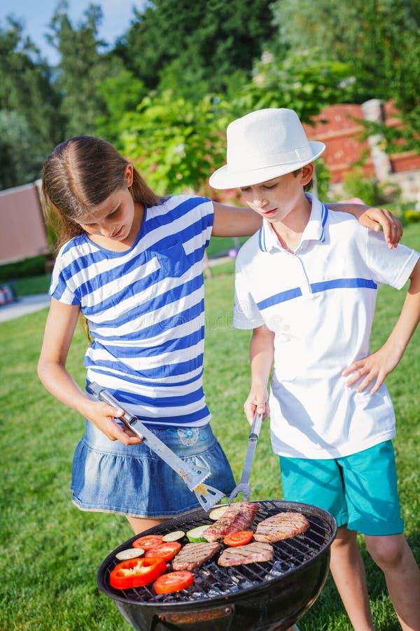 Bambini che hanno un partito del barbecue immagini stock