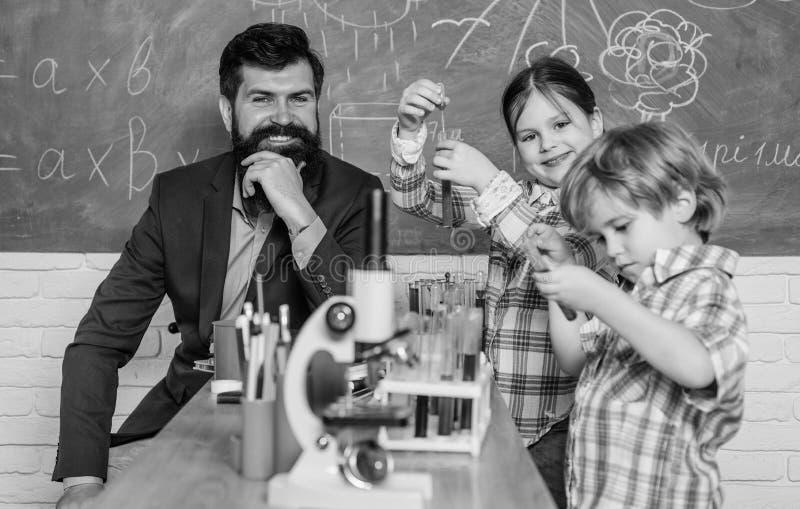 Bambini che imparano chimica nelle note di esperimento del microscopio del laboratorio della scuola strumento ottico del microsco immagine stock