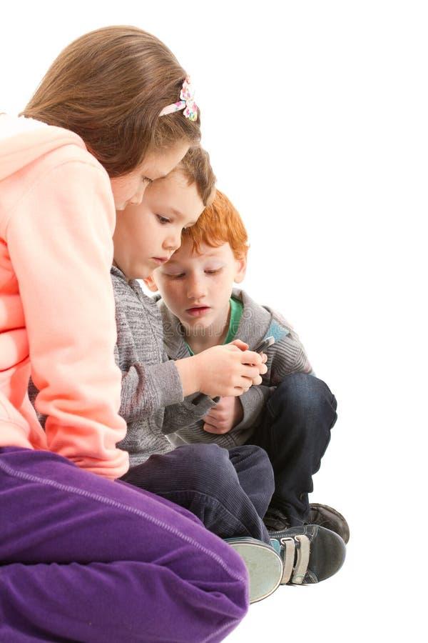 Bambini che inviano gli sms sul telefono cellulare immagine stock libera da diritti