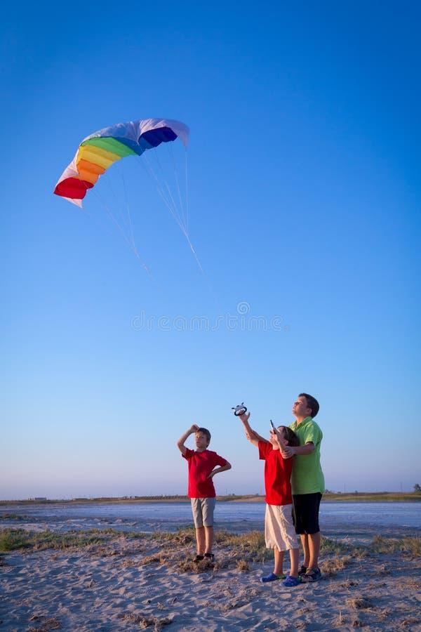 Bambini che lanciano insieme l'aquilone dell'arcobaleno immagine stock