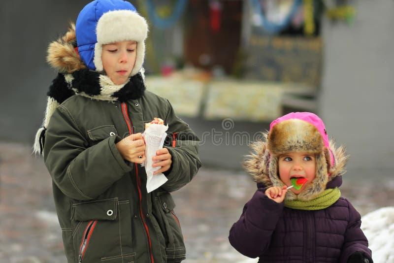 Bambini che mangiano l'alimento della via, ritratto di inverno immagini stock libere da diritti