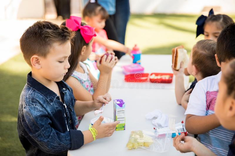 Bambini che mangiano pranzo alla scuola fotografia stock