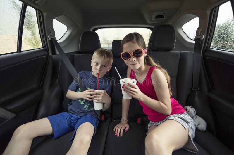 Bambini che mangiano un ossequio nella parte posteriore della loro automobile fotografie stock libere da diritti