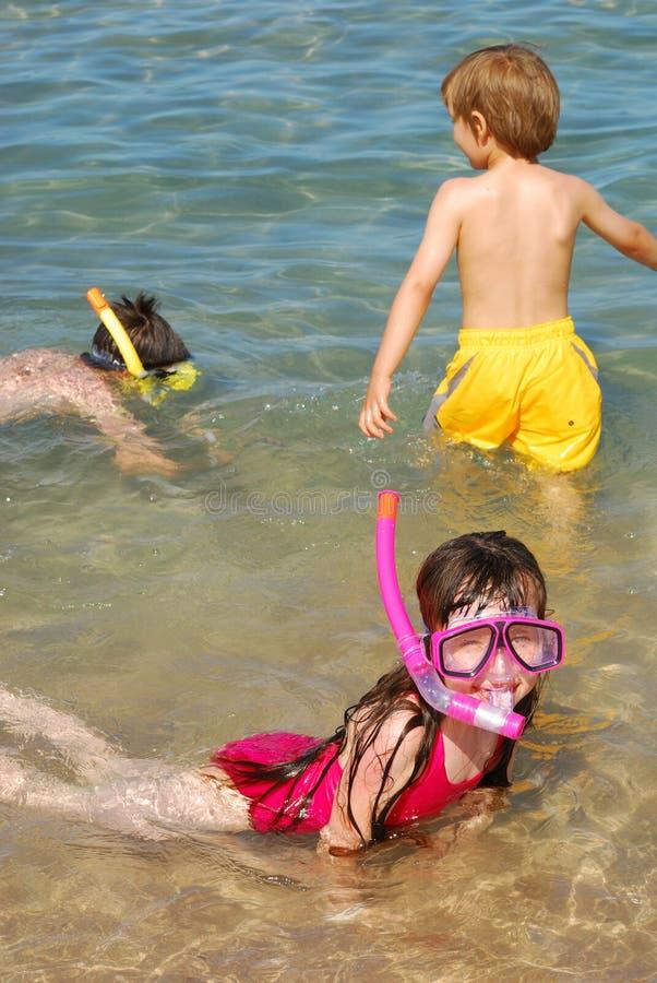 Bambini che navigano usando una presa d'aria alla spiaggia immagini stock libere da diritti