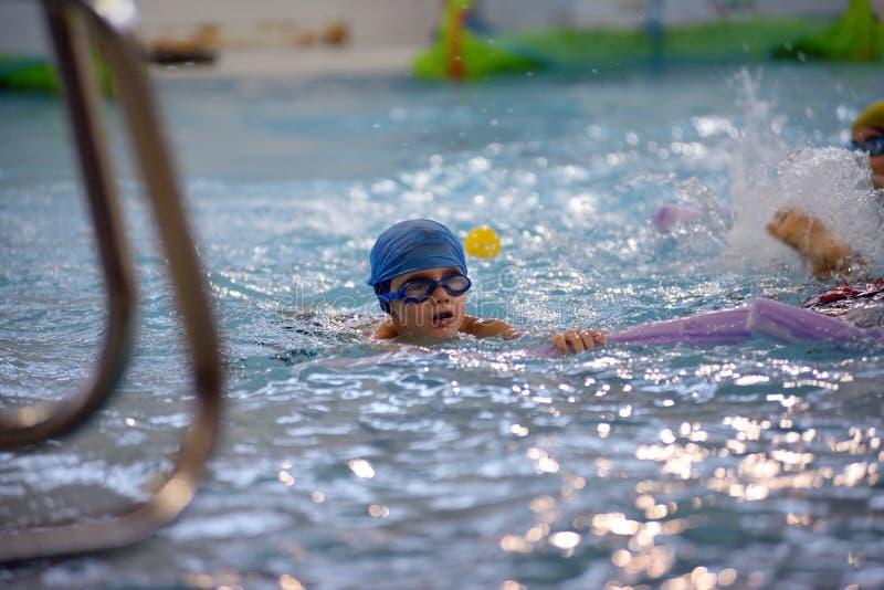 Bambini che nuotano concorrenza in stagno, corsa di relè fotografia stock libera da diritti