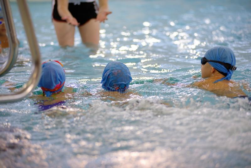 Bambini che nuotano concorrenza in stagno, corsa di relè fotografie stock libere da diritti