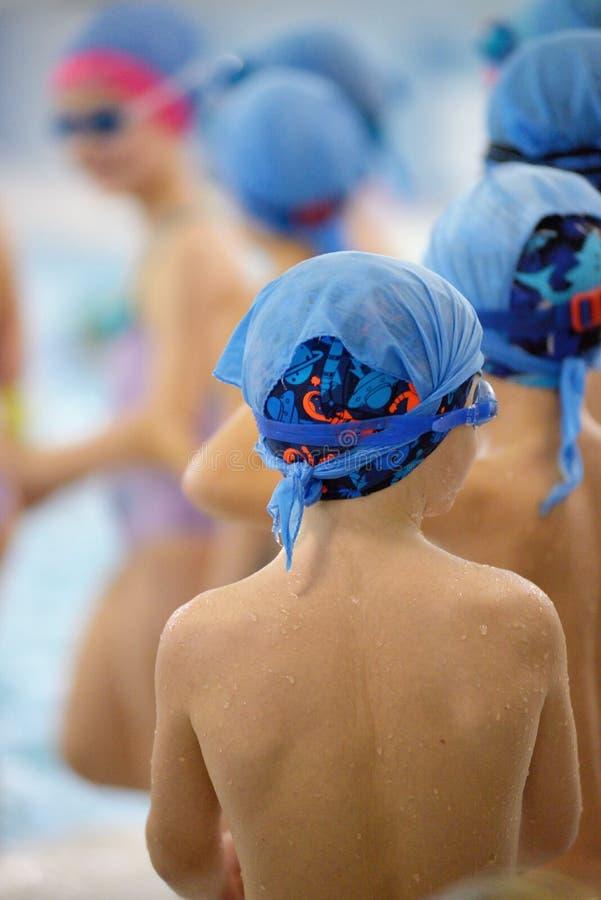 Bambini che nuotano concorrenza in stagno, corsa di relè immagini stock