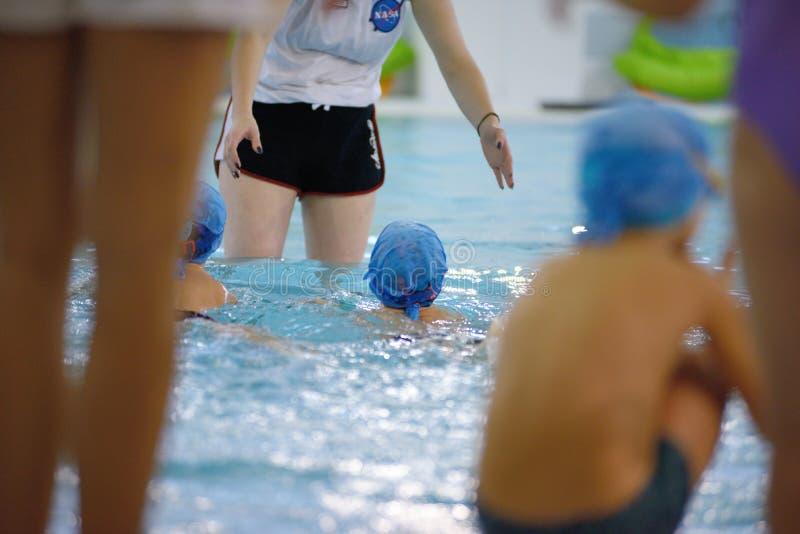 Bambini che nuotano concorrenza in stagno, corsa di relè fotografia stock