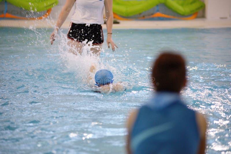 Bambini che nuotano concorrenza in stagno, corsa di relè immagine stock