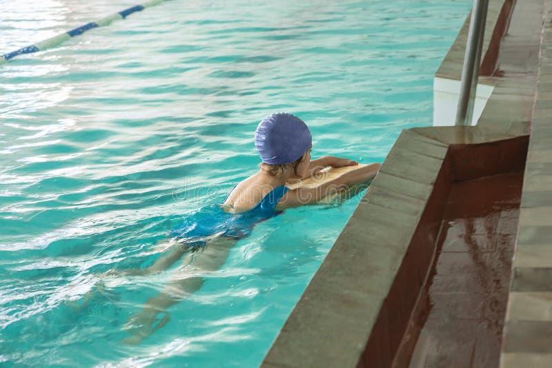 Bambini che nuotano stile libero alla lezione di nuoto fotografia stock libera da diritti
