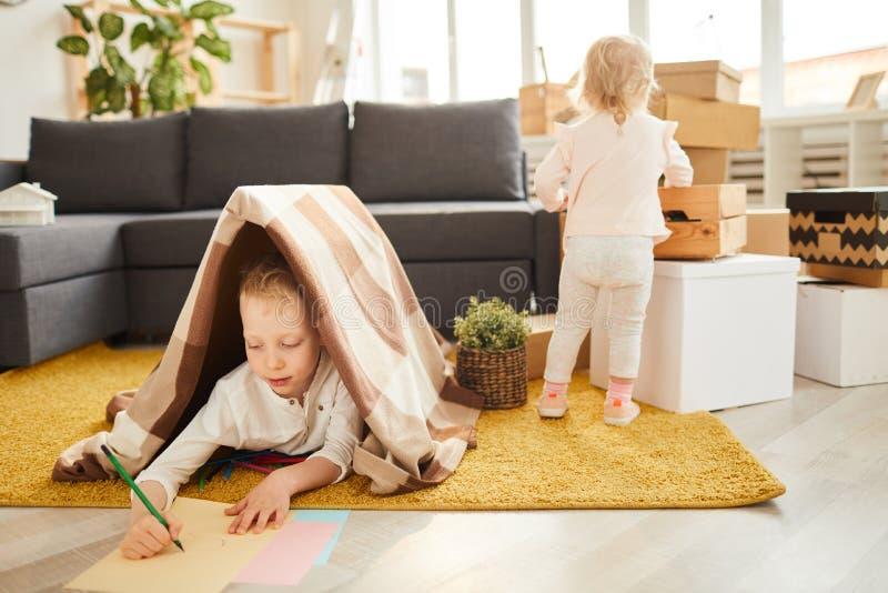 Bambini che ottengono sistemati in nuovo appartamento fotografia stock libera da diritti