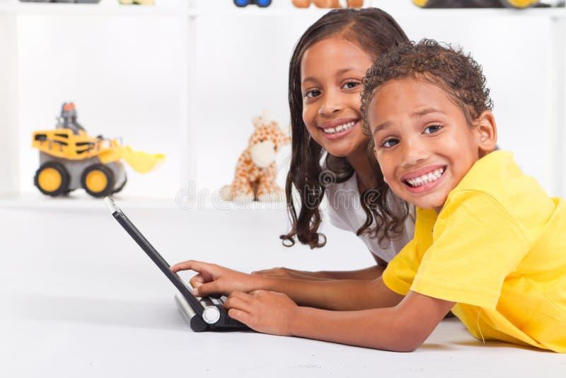 Bambini che per mezzo del calcolatore fotografie stock