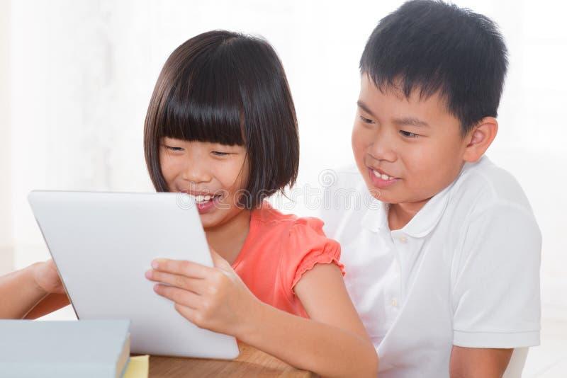 Bambini che per mezzo del pc digitale della compressa fotografia stock
