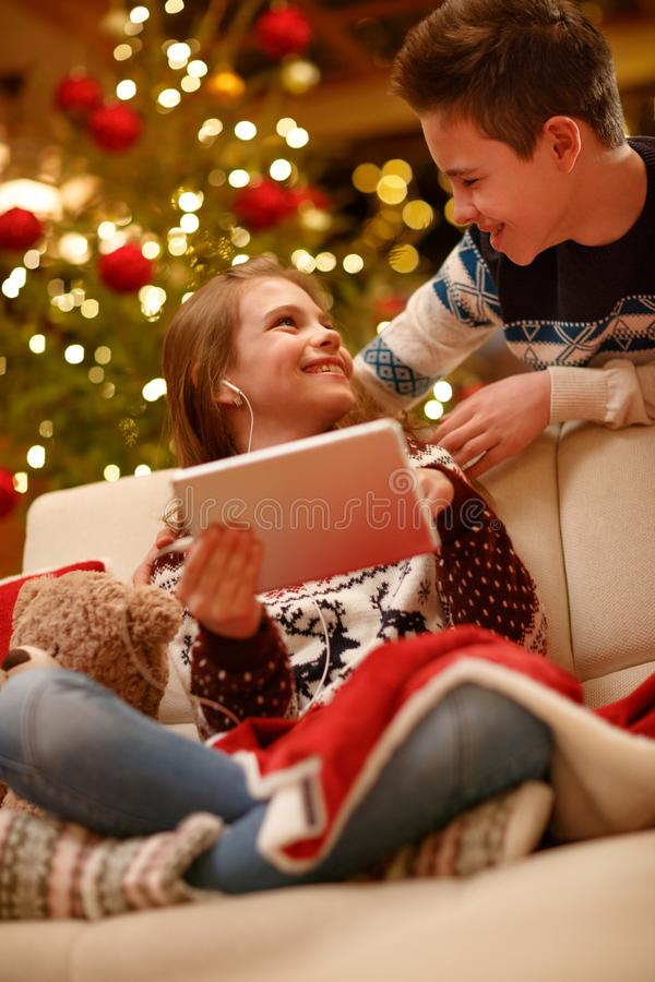 Bambini che per mezzo della compressa digitale sul giorno di Natale immagini stock