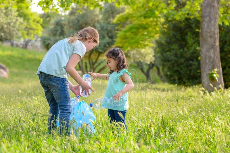 Bambini che puliscono nel parco I bambini volontari con una borsa di immondizia che pulisce la lettiera, mettente la plastica imb immagini stock