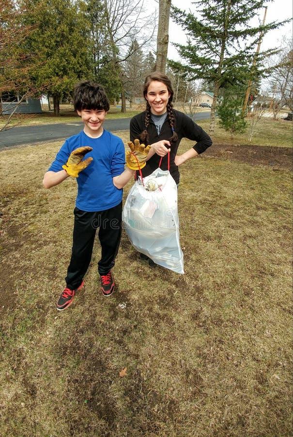 Bambini che raccolgono rifiuti - la Comunità pulisce fotografia stock libera da diritti