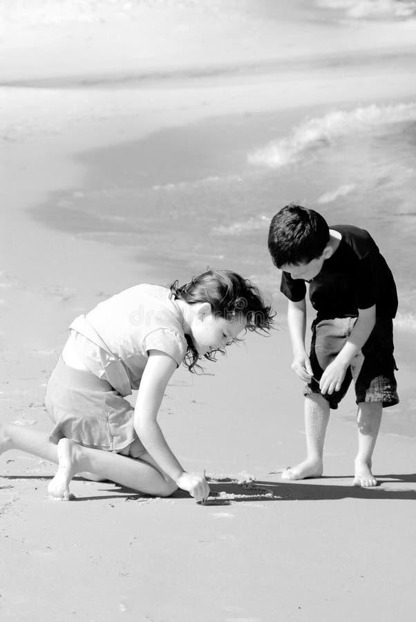 Bambini che scrivono in sabbia della spiaggia fotografie stock libere da diritti