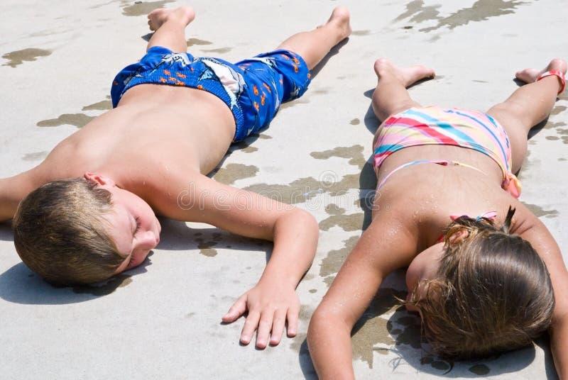 Bambini che si distendono dopo la nuotata immagini stock