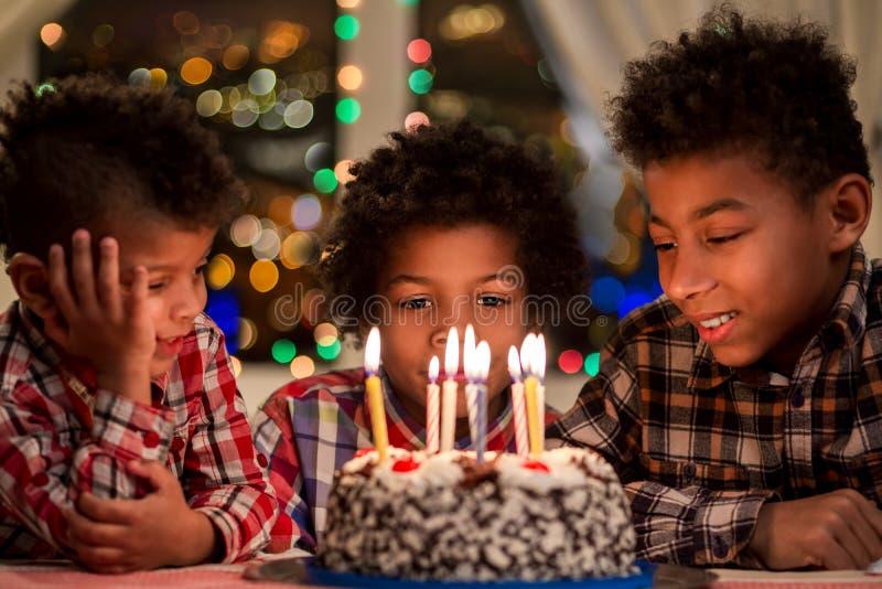 Bambini che si siedono accanto alla torta di compleanno immagini stock libere da diritti