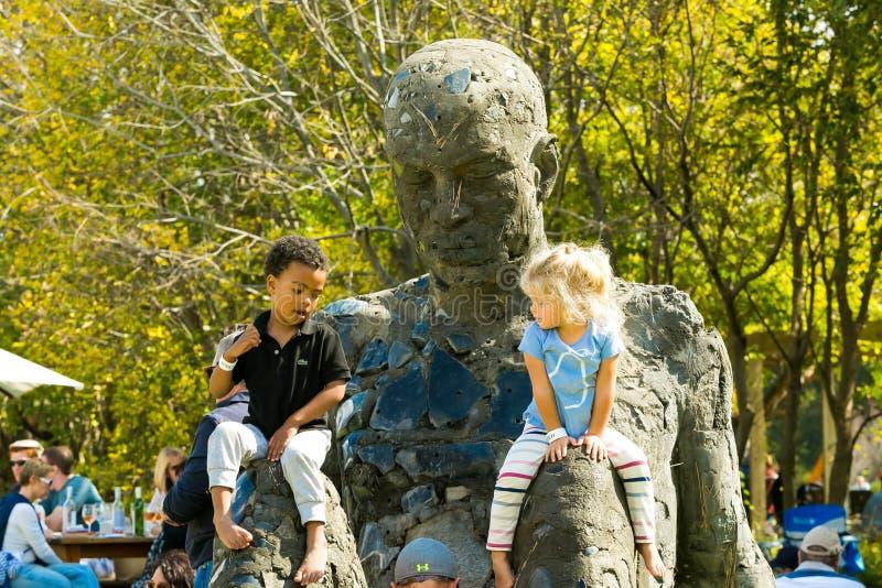 Bambini che si siedono su un pezzo di arte al parco della scultura di Nirox fotografie stock libere da diritti