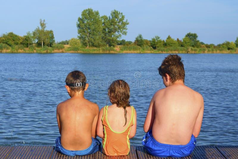 Bambini che si siedono sul pilastro Tre bambini dell'età differente - ragazzo dell'adolescente, ragazzo elementare di età e sedut fotografia stock libera da diritti