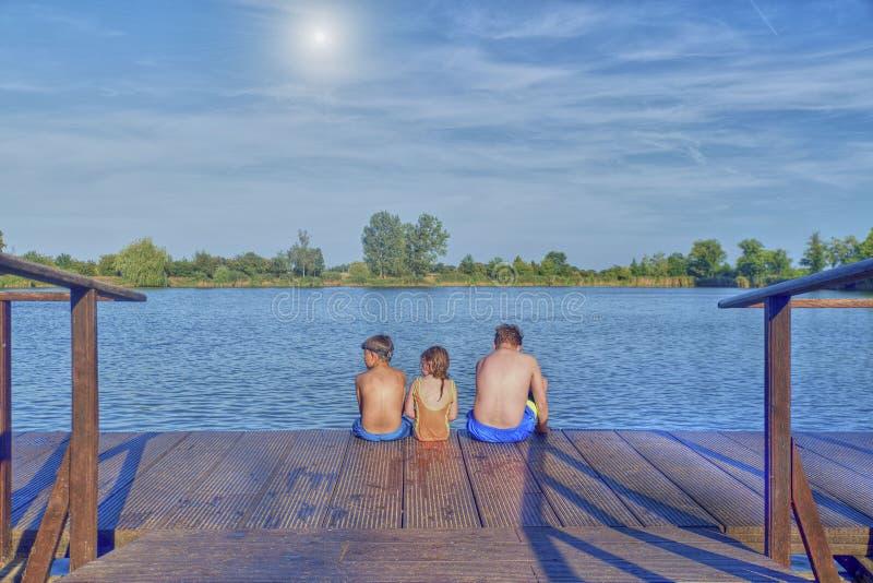 Bambini che si siedono sul pilastro Tre bambini dell'età differente - ragazzo dell'adolescente, ragazzo elementare di età e sedut immagini stock