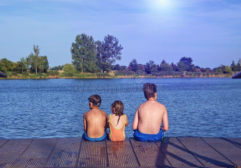Bambini che si siedono sul pilastro Tre bambini dell'età differente - ragazzo dell'adolescente, ragazzo elementare di età e sedut fotografie stock