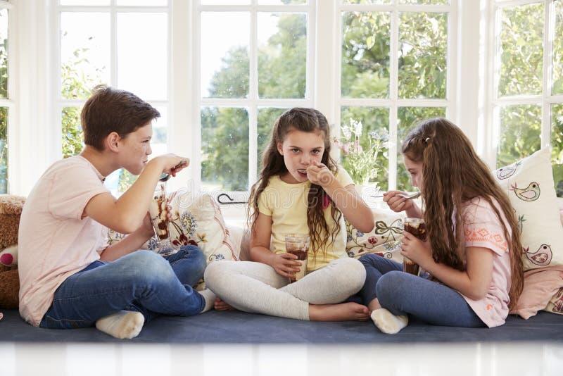 Bambini che si siedono sulla finestra Seat che mangia le coppe gelato fotografia stock libera da diritti