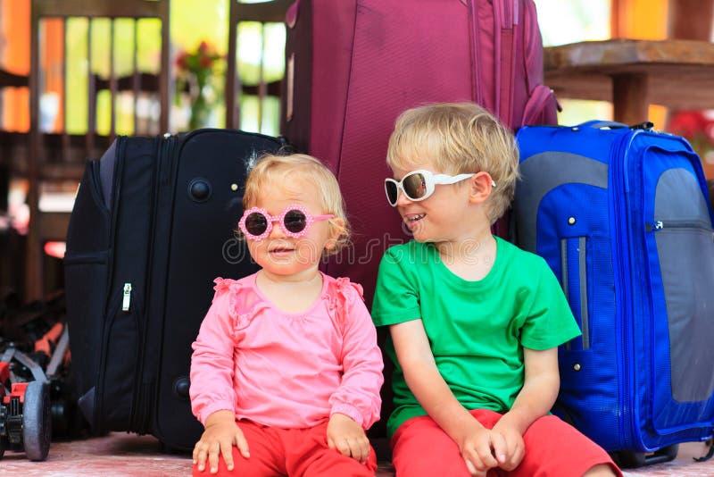 Bambini che si siedono sulle valigie pronte a viaggiare fotografie stock
