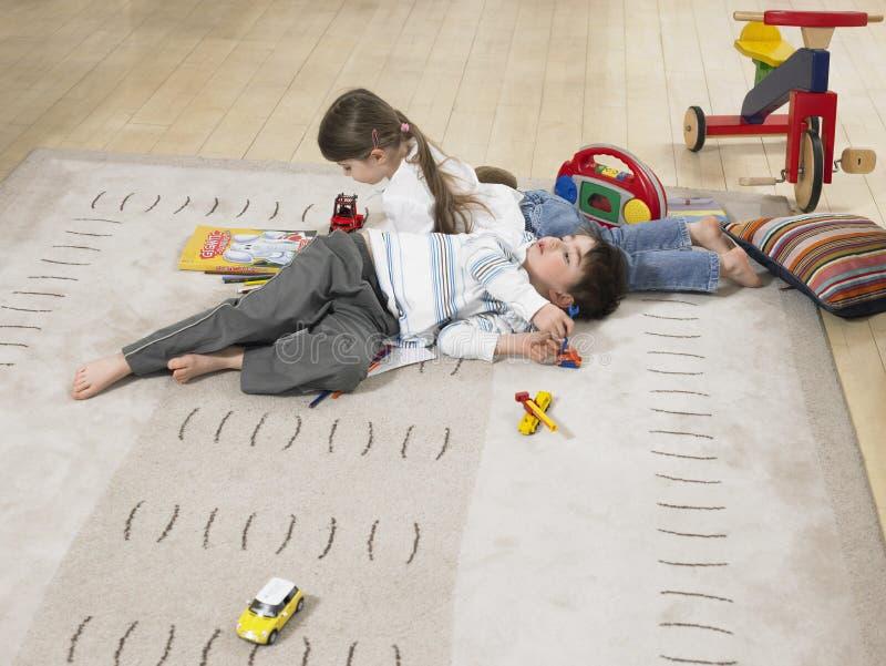 Bambini che si trovano sulla coperta a casa immagini stock