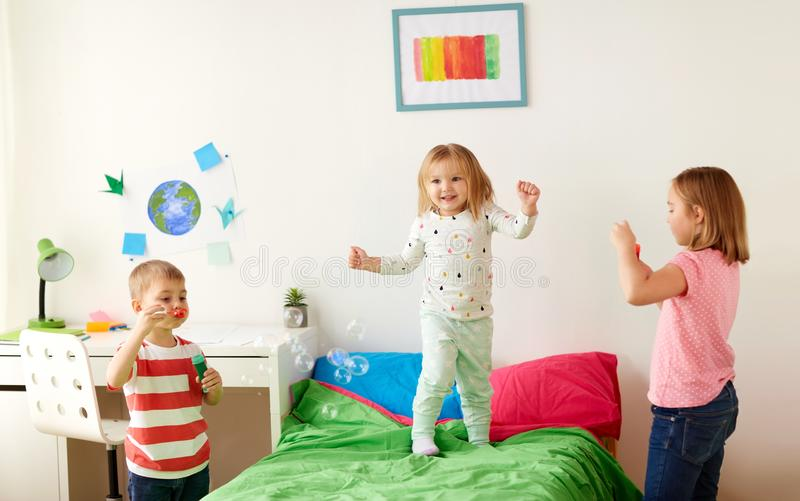 Bambini che soffiano le bolle di sapone e che giocano a casa immagine stock