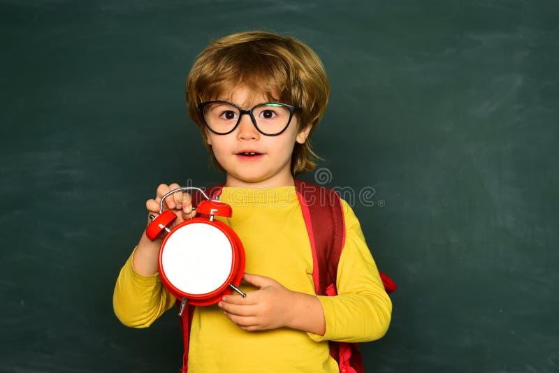 Bambini che sono recenti per la lezione 1? settembre Ansia della sveglia late Allarme dell'orologio della tenuta del ragazzo del  fotografia stock