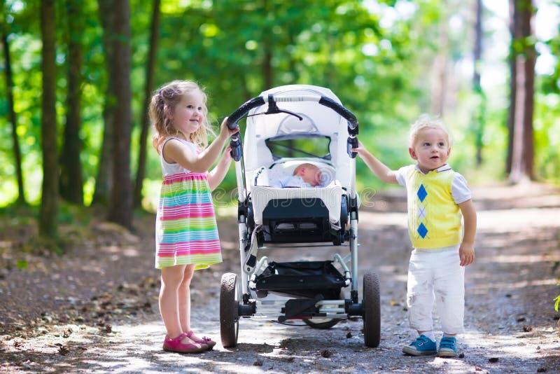 Bambini che spingono passeggiatore con il neonato fotografia stock libera da diritti
