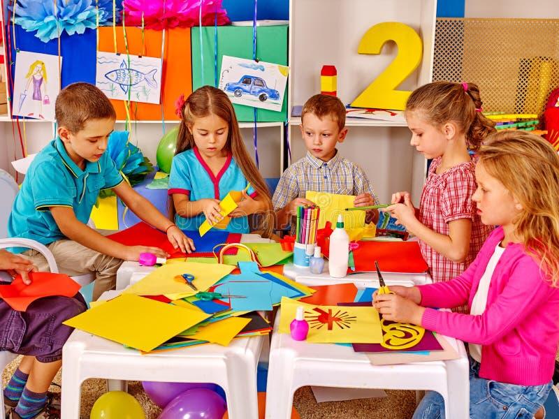Bambini che tengono carta colorata sulla tavola nell'asilo fotografia stock