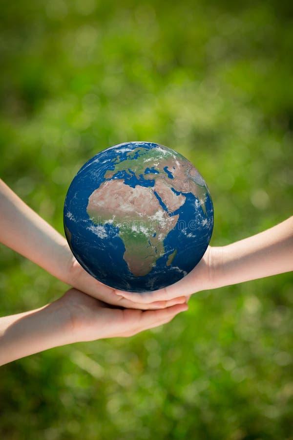 Bambini che tengono il pianeta della terra in mani immagine stock libera da diritti