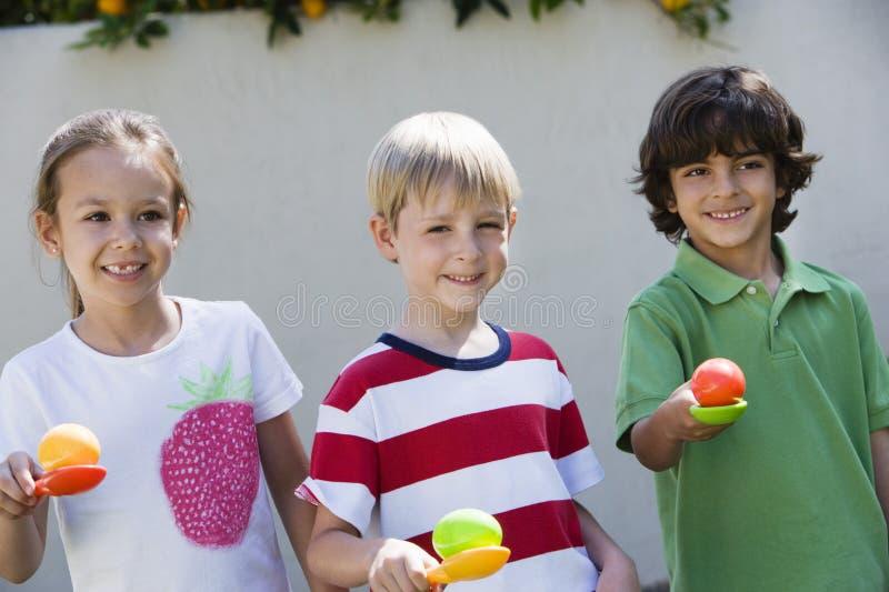 Bambini che tengono le uova in cucchiai per la corsa dell'uovo immagine stock libera da diritti