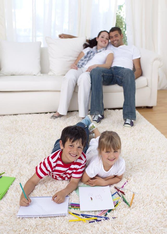 Bambini che verniciano sul pavimento in salone fotografia stock libera da diritti