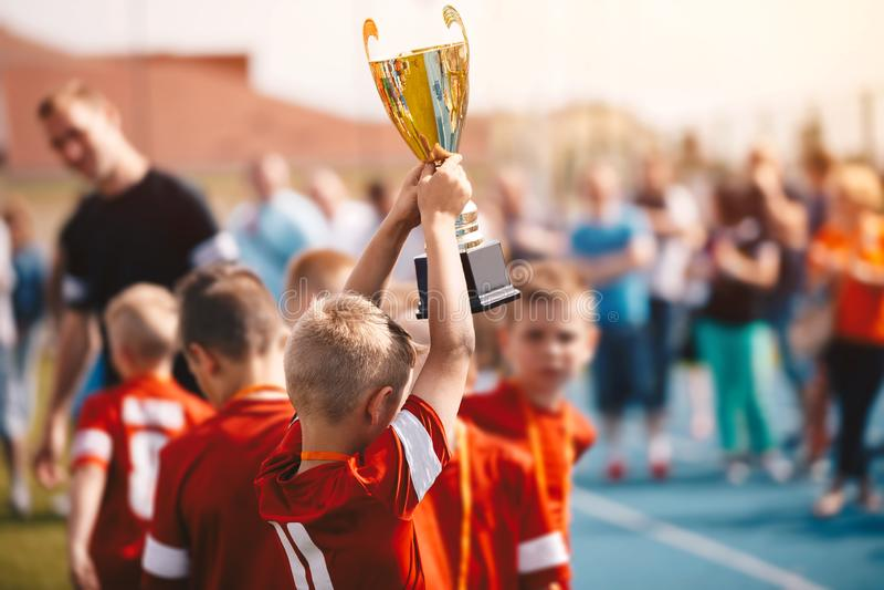 Bambini che vincono la concorrenza di sport Squadra di calcio dei bambini con il trofeo Ragazzi che celebrano campionato di calci fotografia stock libera da diritti