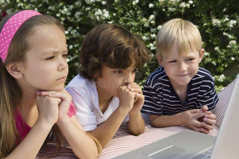 Bambini colpiti che esaminano computer portatile fotografia stock libera da diritti