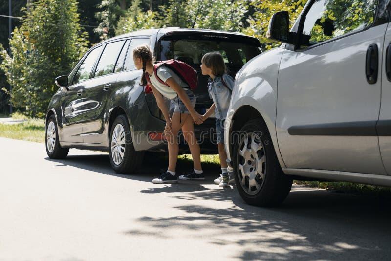 Bambini con gli zainhi fra le automobili che provano a camminare tramite la strada immagine stock