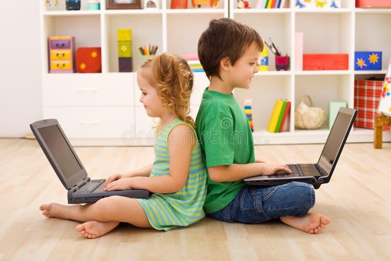 Bambini con i computer portatili - generazione di calcolatore fotografia stock libera da diritti