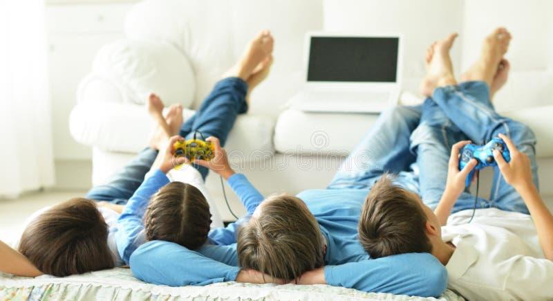 Bambini con i genitori che giocano i giochi di computer immagine stock