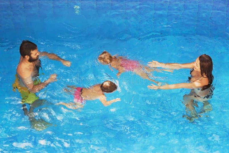 Bambini con i genitori che nuotano underwater nello stagno blu immagine stock libera da diritti