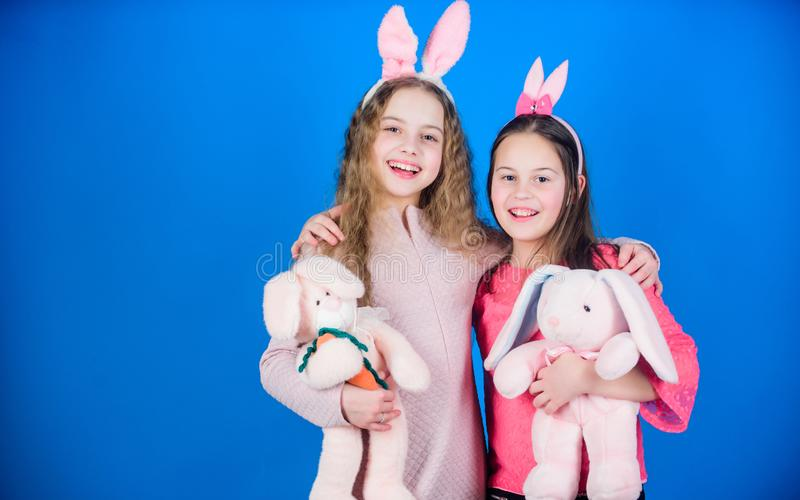 Bambini con i giocattoli del coniglietto su fondo blu Sorelle costumi svegli sorridenti del coniglietto Gioia e felicità sparse i immagini stock