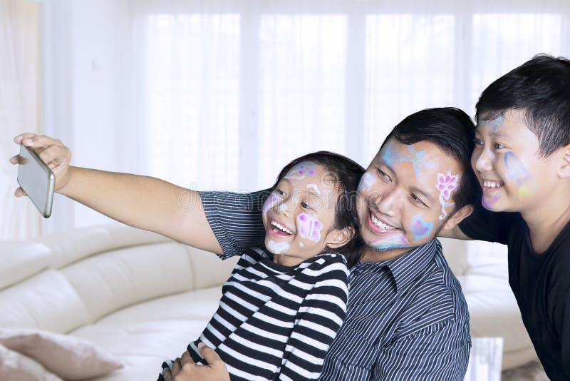 Bambini con il padre che prende insieme foto a casa immagini stock