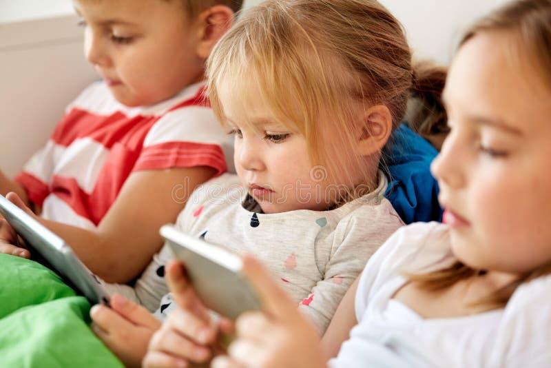 Bambini con il pc e lo smartphone della compressa a letto a casa immagine stock