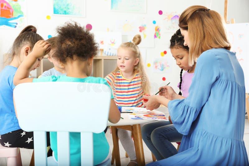Bambini con l'insegnante femminile alla lezione della pittura fotografia stock